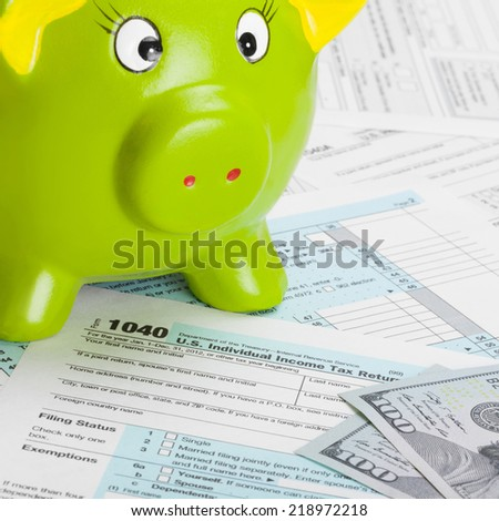 US Tax Form 1040 with green piggy bank and dollars - 1 to 1 ratio - stock photo