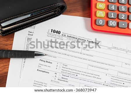 US tax form with pen,wallet and calculator selective focus / taxation concept