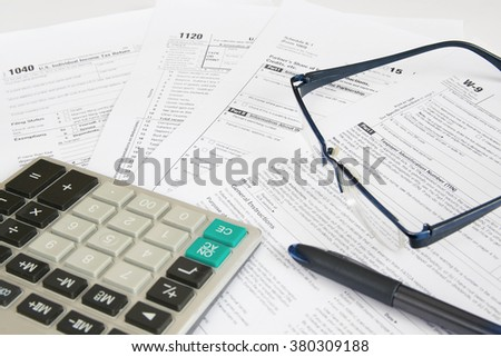 US tax forms with calculator,  glasses and pen. - stock photo