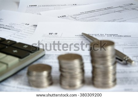 US tax forms with calculator, pen and coins. Shallow depth of field. - stock photo
