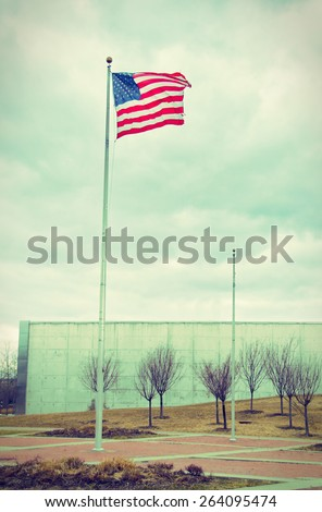 US United States Flag handing proudly over the the Liberty State Park 9/11 Memorial in New Jersey - vintage retro look - stock photo