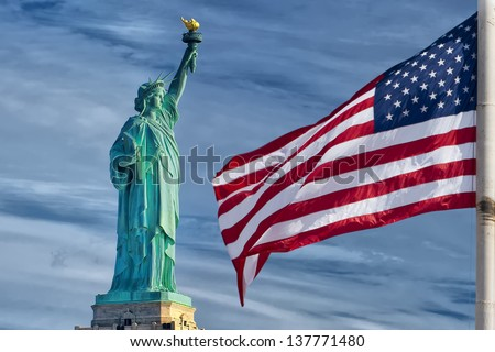 Usa American flag stars and stripes on statue of liberty blue sky background - stock photo