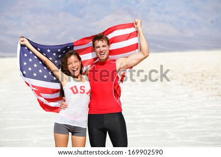 USA athletes people holding american flag cheering. Sports man and fitness runner woman celebrating winning after running. Happy young multicultural fitness couple in excited celebration outside. - stock photo