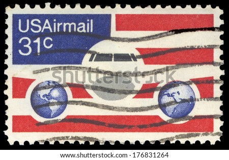 USA-CIRCA 1976: A 21 cent United States Airmail postage stamp, shows image of Plane and Globes on red white and blue background, circa 1976. - stock photo