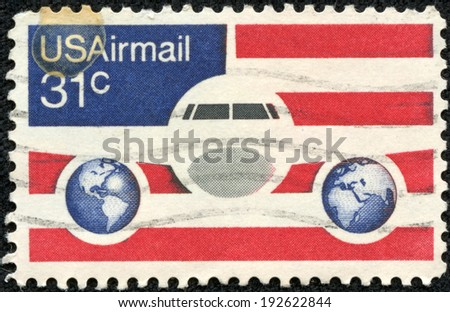 USA-CIRCA 1976: A 31 cent United States Airmail postage stamp, shows image of Plane and Globes on red white and blue background, circa 1976. - stock photo