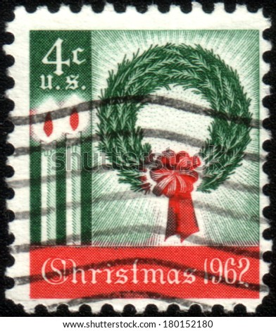 USA - CIRCA 1962: America's first Christmas postage stamp shows a wreath and candles. It was well received and started a long tradition of a new Christmas stamp each year, circa 1962  - stock photo
