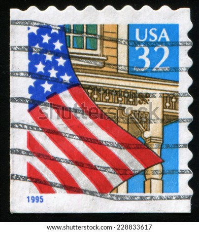 USA CIRCA 1995: stamp printed in United States shows American flag on the background of  house and  blue sky, circa 1995