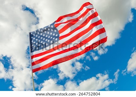 USA flag and cumulus clouds on background - stock photo