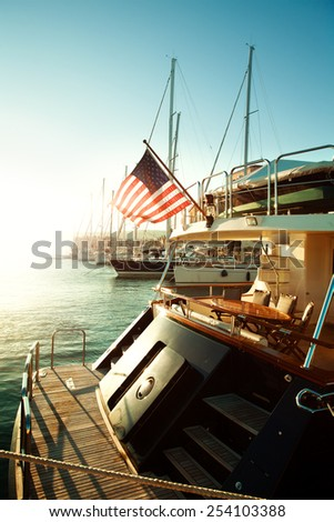 USA flag and yacht on sea, start of American journey - stock photo