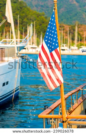 USA flag on the background of the masts of yachts in the port - stock photo