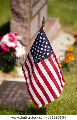 USA flag placed by Veteran's tombstone. - stock photo
