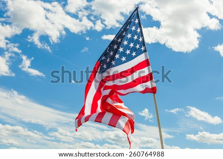 USA flag with clouds on background - outdoors shoot - stock photo
