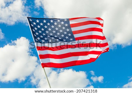 USA flag with white clouds on background - stock photo
