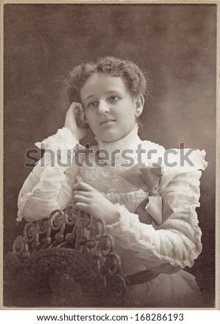 USA - ILLINOIS - CIRCA 1898 - A vintage Cabinet Card  photo of a beautiful young woman sitting. The woman is dressed in a Victorian style dress. A photo from the Victorian era. CIRCA 1898
