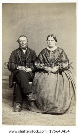 USA - ILLINOIS - CIRCA 1863 Vintage carte de visite photo of older couple sitting. She is dressed in hoop skirt dress. He is dressed in suit. This photo from the Civil War Victorian era. CIRCA 1863