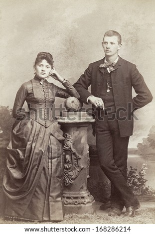 USA - INDIANA - CIRCA 1885 - A vintage photo of a young couple. They are both standing. The woman is dressed in a Victorian bustle style dress. A photo from the Victorian era. CIRCA 1885 - stock photo