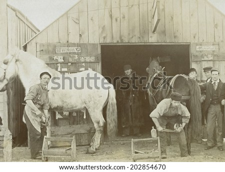 USA - KANSAS - CIRCA 1890 Vintage photo of a blacksmith's shop. There are two workers shoeing two horses. The shop is a wooden building. This photo is from the Victorian era. CIRCA 1890 - stock photo
