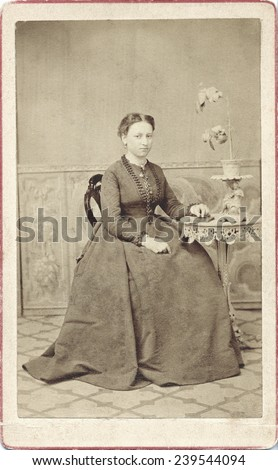 USA MASSACHUSETTS CIRCA 1870 A Vintage Carte De Visite photo of a young woman sitting in a chair. She is wearing a hoop skirt. Photo from the civil war victorian era. CIRCA 1870 - stock photo