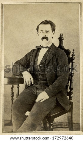 USA - MASSACHUSETTS - CIRCA 1864 - A vintage Cartes de visite photo of a gentleman. The man is sitting with one arm on the arm of the chair. A photo from the Civil War Victorian era. CIRCA 1864 - stock photo