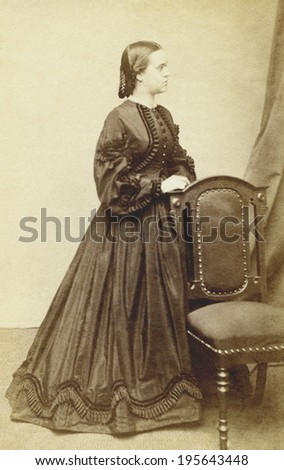 USA - MASSACHUSETTS - CIRCA 1865 Vintage carte de visite photo ofl young woman standing and looking to one side dressed in hoop skirt dress. This photo from the Civil War Victorian era. CIRCA 1865 - stock photo