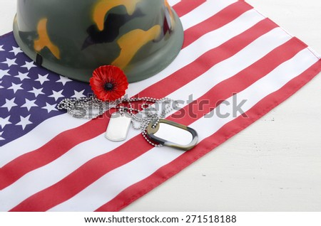 USA Memorial Day concept with dog tags and red remembrance poppy on American stars and stripes flag on white vintage wood table with copy space.  - stock photo