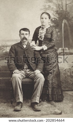 USA - MICHIGAN - CIRCA 1880 Vintage Carte de Viste photo of young couple. The gentleman is sitting and the lady is standing dressed in a Victorian style dress. Photo from Victorian era. CIRCA 1880 - stock photo