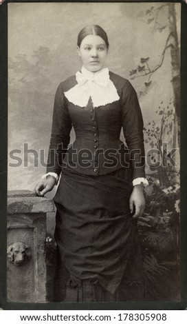 USA - MINNESOTA - CIRCA 1885 - A vintage Cartes de visite photo of young woman standing next to table dressed in Victorian style bustle dress with fancy collar. Photo from Victorian era. CIRCA 1885 - stock photo