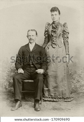 USA - NEW JERSEY - CIRCA 1890 - A vintage photo of a young couple. The husband is sitting and the wife is standing and is dressed in a Victorian style dress. A photo from the Victorian era. CIRCA 1890