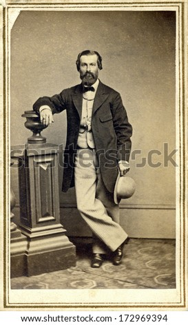 USA - NEW YORK - CIRCA 1865 - A vintage Cartes de visite photo of a gentleman. The man is standing with one arm on a post. A photo from the Civil War Victorian era. CIRCA 1865 - stock photo