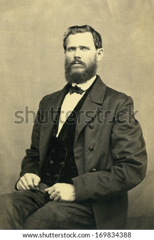 USA - NEW YORK - CIRCA 1898 - A vintage photo of a young man. The man is sitting. He has a beard and mustache and is dressed in suit and vest with bow tie. A photo from the Victorian era. CIRCA 1898  - stock photo