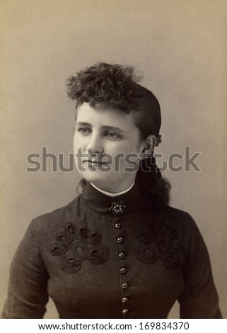USA - NEW YORK - CIRCA 1885 - A vintage photo of a young woman. The portrait is a woman dressed in a beautiful Victorian style dress. A photo from the Victorian era. CIRCA 1885  - stock photo