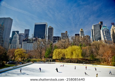 USA, New York, 30.03.2007: Skating Rink in Central Park, ride people on the background of colorful trees, skyscrapers, The Plaza Hotel - stock photo