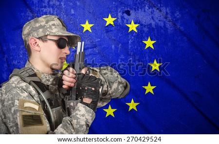 USA soldier with gun on a European Union flag background - stock photo