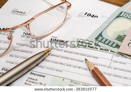 USA tax form 1040EZ for year 2016 with pen and glasses