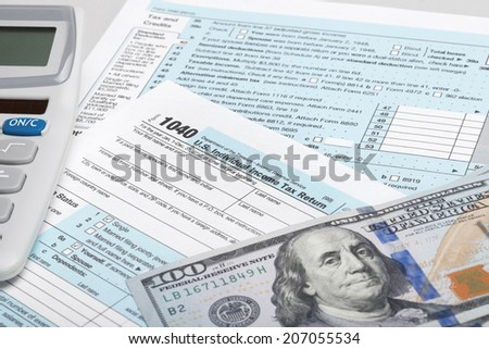 USA Tax Form 1040 with calculator and 100 US dollar bills