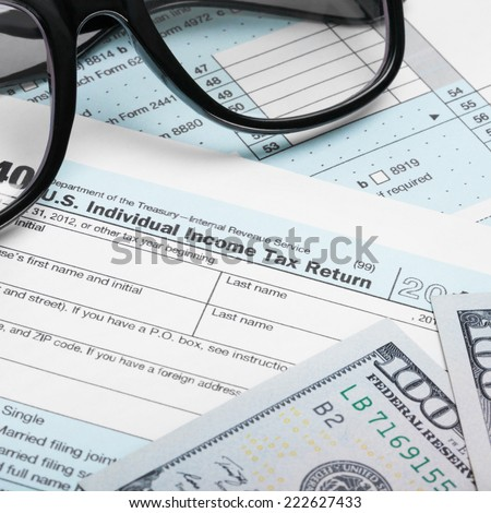 USA Tax Form 1040 with glasses and dollars bills - 1 to 1 ratio