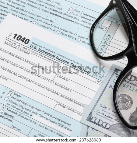 USA 1040 Tax Form with glasses and 100 US dollar bills - stock photo
