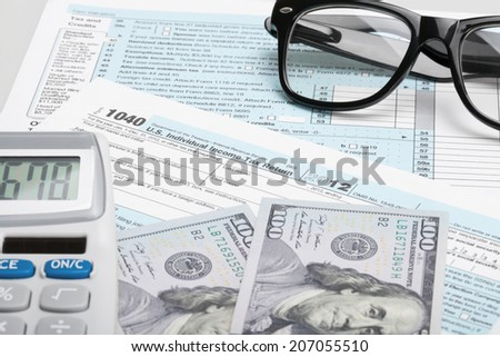 USA Tax Form 1040 with glasses, calculator and 100 US dollar bills - stock photo