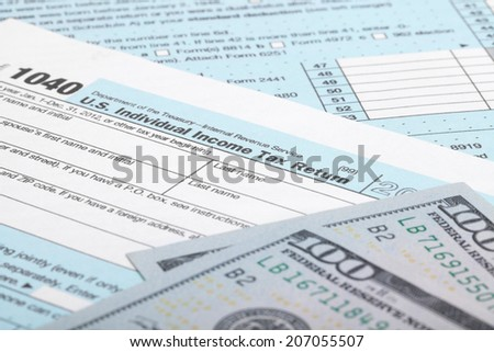 USA Tax Form 1040 with 100 US dollar bills