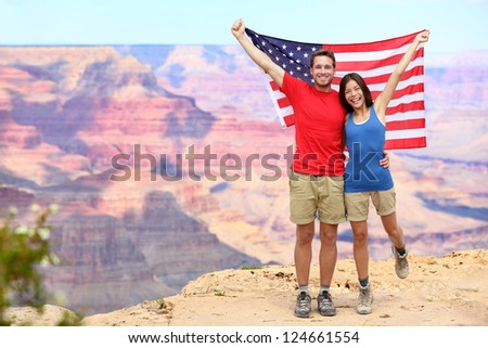 USA travel tourist couple holding american flag in Grand Canyon. Happy young multiethnic couple cheering at Grand Canyon south rim during summer holidays. - stock photo