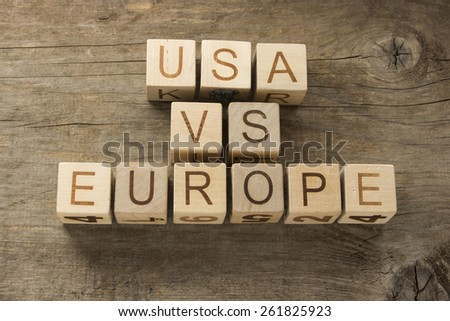 USA vs EUROPE text on a wooden background