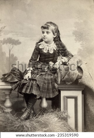 USA WISCONSIN CIRCA 1890 Vintage Cabinet Card of beautiful young girl in dress with lace collar. She is sitting with long curly hair. Her hair is long with bangs. Photo from Victorian era. CIRCA 1890 - stock photo