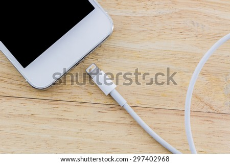 USB cable for smartphone on wood background. - stock photo