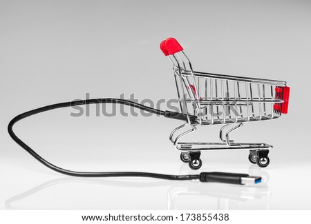 USB cable plugged in a small shopping cart on a white reflective background. - stock photo