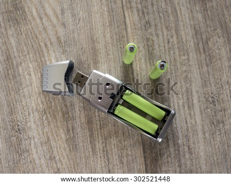 USB charger and green AAA batteries - stock photo