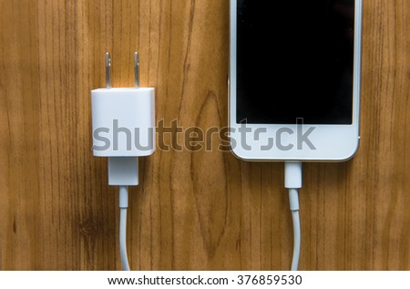 USB charger with smartphone on wood table - stock photo
