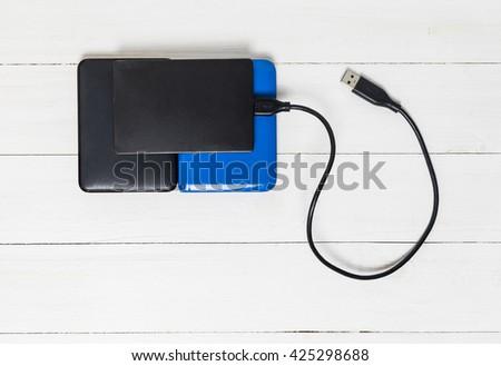 USB External Hard disks on wooden background - stock photo