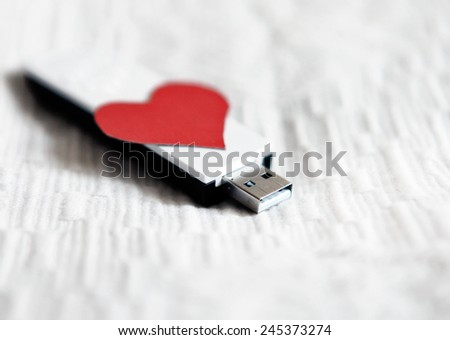 USB Flash Drive with Heart Shape on the White Fabric Background - stock photo