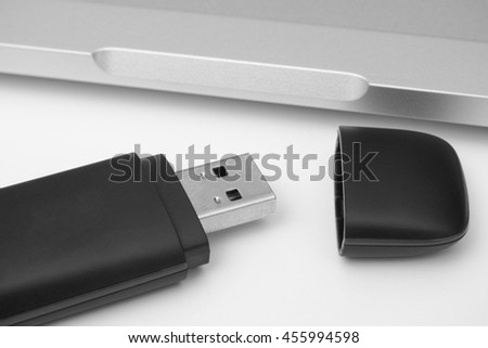 USB Flash Drive with laptop in the background. Black and white. Close up.
