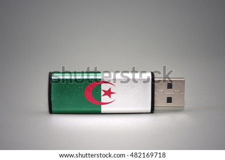 usb flash drive with the national flag of algeria on gray background. concept